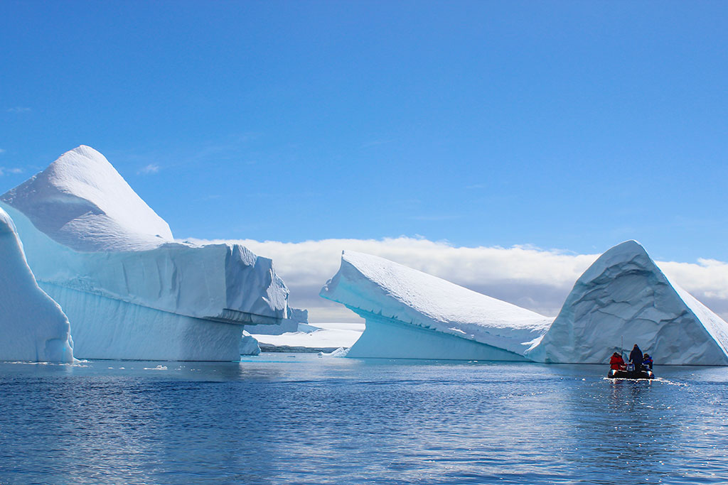 People cruising in Zodiac by icebergs in Antarctica