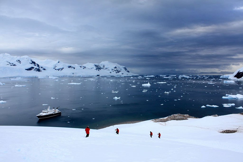 Hiking in Antarctica near penguin colony with Hanse Explorer Expedition Yacht in background