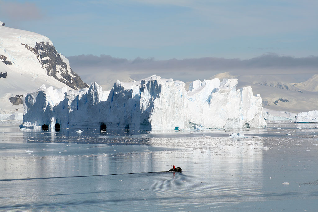 Zodiac boat in Antarctica with castle iceberg