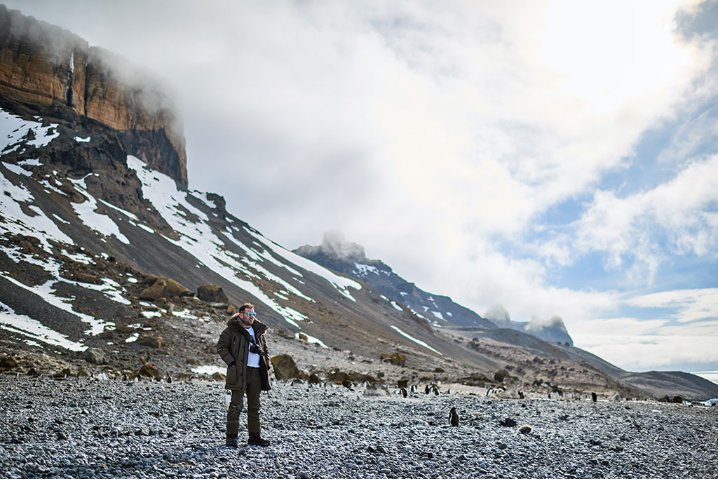 Man standing in front of Brown Bluff in Antarctica