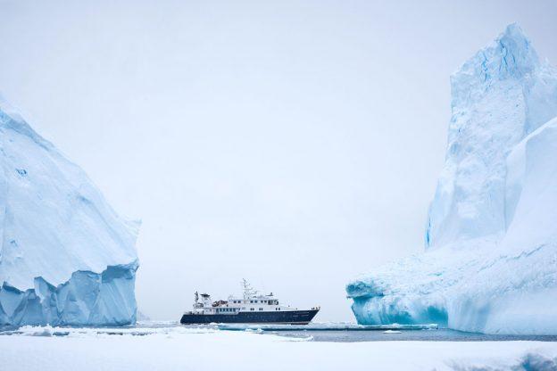 Yacht Hanse Explorer and icebergs in Antarctica